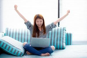 jeune femme asiatique utilisant un ordinateur portable travaille sur un canapé. photo