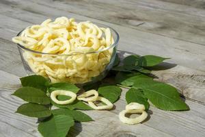 chips. rondelles d'oignon dans un plat en verre sur un fond en bois photo