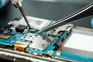 technicien réparant l'intérieur du disque dur en fer à souder. photo