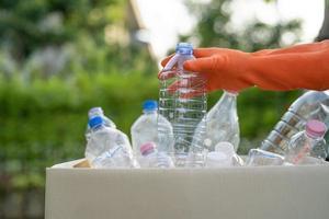 femme asiatique volontaire porter des bouteilles en plastique d'eau dans les ordures ménagères photo