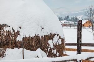 botte de foin recouverte de chapeau de neige en hiver photo