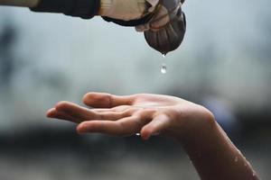 la main attrape les gouttes d'eau qui sortent du robinet photo