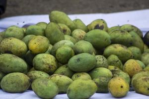 un tas de mangues sur l'étal du vendeur dans un marché traditionnel photo