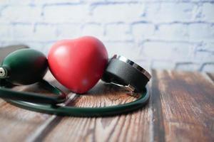 machine de tension artérielle et forme de coeur sur le fond blanc photo