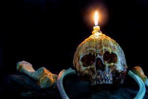 crâne avec bougie sur le dessus et os sur bois grunge photo