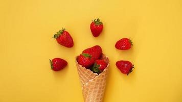 cornet de crème glacée aux fraises sur fond jaune photo