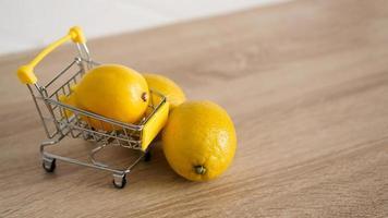 citron dans un chariot de supermarché sur fond de cuisine photo