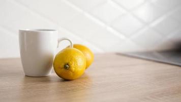 deux citrons sur la table de la cuisine près d'une tasse de thé blanc photo