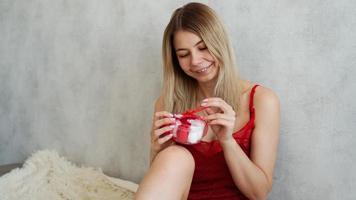portrait d'une jolie fille reçoit une boîte-cadeau, profitant d'un cadeau à la maison photo