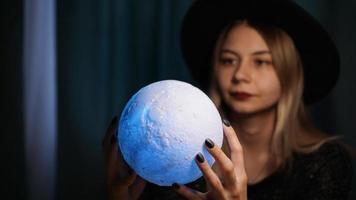 une jeune femme diseuse de bonne aventure dans un chapeau tient une boule magique. photo