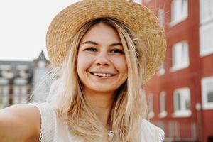 Jeune fille blonde gaie souriante au chapeau faisant selfie photo
