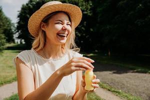 fermer le portrait d'une femme blonde au chapeau de paille. elle rit photo