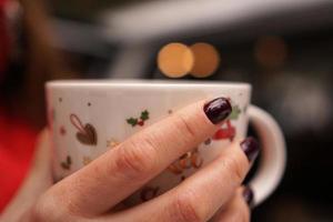 mains féminines tenant une tasse avec une boisson chaude et noire à l'extérieur le jour de l'hiver photo