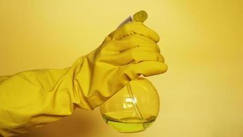 main dans un gant en caoutchouc jaune tenant un spray en plastique photo