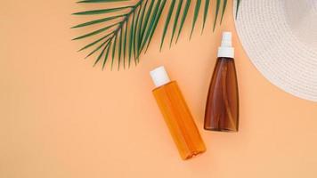 crème solaire, chapeau de soleil, bouteille de lotion sur fond orange doux photo