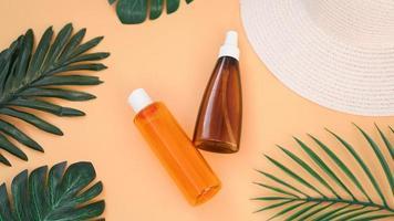 crème solaire, chapeau de soleil, bouteille de lotion sur orange douce photo