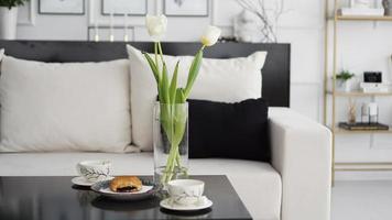 canapé dans un intérieur moderne. sur la table il y a un bouquet de tulipes photo