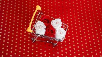 fleur de roses rouges et blanches sur panier sur rouge photo