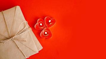 enveloppes en papier kraft avec des bougies rouges sur fond rouge. photo