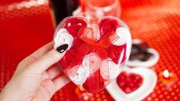 mains de femme tenant une boîte-cadeau en forme de coeur avec une belle rose photo