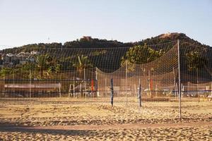 terrain de volley-ball sur la plage d'alanya, en turquie. palmiers et montagnes photo