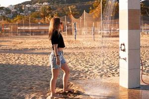 une fille en short et un t-shirt noir sur la plage près de la douche. photo