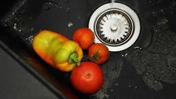 légumes - tomates et poivrons dans un évier de cuisine noir sous l'eau photo