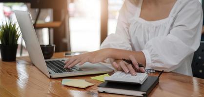gros plan sur un homme d'affaires utilisant une calculatrice et un ordinateur portable pour calculer photo