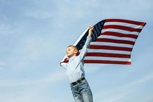 un petit garçon tient un drapeau des états-unis contre le ciel photo