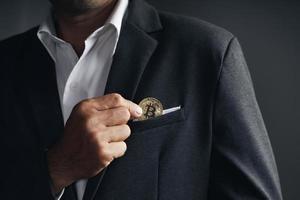 un homme d'affaires investisseur a mis un bitcoin doré dans la poche du costume. photo