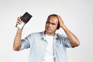 homme tenant son portefeuille vide sur fond blanc. pas d'argent. photo