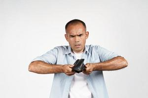 homme tenant la tête en bas et regardant à l'intérieur de son portefeuille vide photo