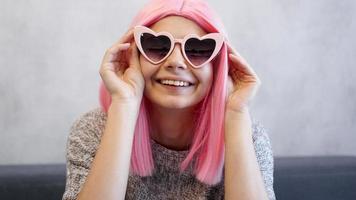 femme portant des lunettes et perruque rose - portrait positif photo
