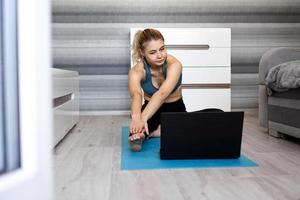 femme en tenue de sport regardant une vidéo en ligne sur un ordinateur portable photo