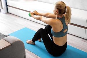 femme athlétique faisant des exercices d'entraînement d'haltères à la maison photo