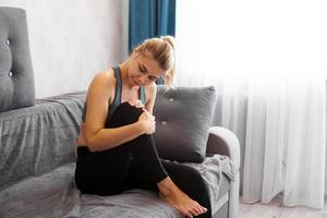 femme a une douleur à la rotule assise sur un canapé se sentant tellement malade photo