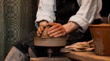 mains de potier faisant en argile sur tour de potier photo