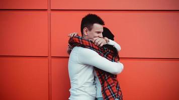 couple datant et étreignant dans l'amour dans une journée ensoleillée - fond rouge photo