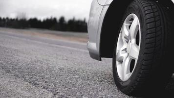 roue de voiture argentée sur la route. photo dans les tons gris