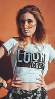 mode portrait élégant jolie femme à lunettes de soleil posant dans la ville photo