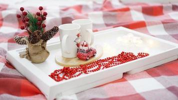 tasse rouge de nouvel an ou de noël sur un plateau blanc au lit avec des lumières photo