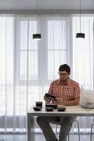 Jeune homme triant les boîtes de livraison de nourriture dans la cuisine moderne photo
