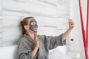 femme avec masque facial relaxant assise sur le lit à l'aide d'un appareil mobile photo