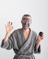 femme heureuse appliquant un masque facial dans la salle de bain photo