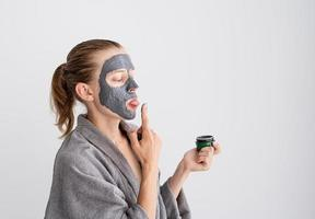 femme drôle heureuse appliquant un masque facial et l'essayant photo