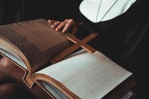 nonne en costume noir de religion détient la bible. notion de religion photo