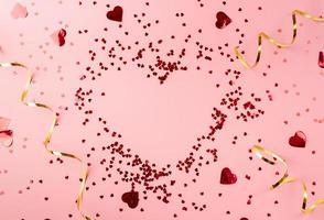 forme de coeur rouge coeur confetti vue de dessus à plat sur fond rose photo