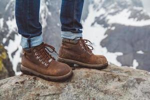 jambes d'un homme en chaussures marron sur fond de montagnes photo