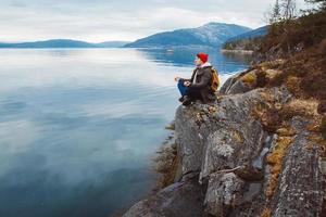 homme voyageur dans une position méditative assis sur un rivage rocheux photo