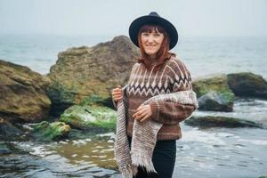 portrait de femme dans un chapeau et une écharpe sur fond de mer et de rochers photo